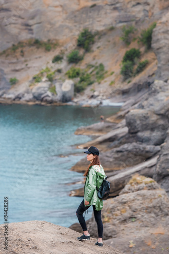 Aluminium Prints Cathedral Cove Girl sitting on the rock near to the seaside, resting after hiking. Woman in sportswear, healthy lifestyle. Successful hiker hiking on seaside mountain peak
