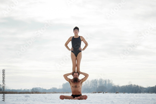 A man and a middle-aged woman practicing yoga on a frozen river. A pair of yoga.