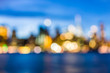 canvas print picture - Bokeh of NYC New York City downtown lower financial district Brooklyn Bridge skyscrapers, east river, cityscape skyline during evening dark blue sunset, dusk, twilight