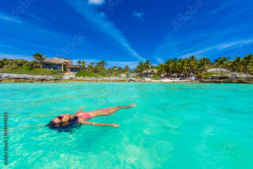 Papiers peints Recifs coralliens Attractive young woman relaxing in turquoise waters of Caribbean Sea in front of paradise beach in Tulum, close to Cancun, Riviera Maya, Mexico