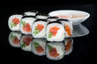 Japanese cuisine. Appetizing maki sushi rolls with rice, salmon, salmon and cucumber on dark background