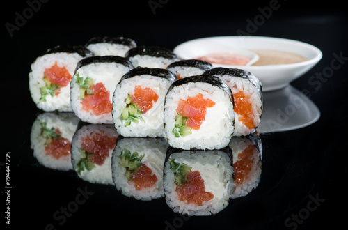 Fototapeta Japanese cuisine. Appetizing maki sushi rolls with rice, salmon, salmon and cucumber on dark background obraz