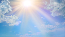 Miraculous Heavenly Light -  Blue Sky, Fluffy Clouds And A Beautiful Warm Orange Yellow Sun Beaming Down Radiating Depicting A Holy Entity