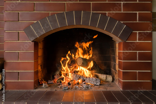 Cuadros en Lienzo A brick fireplace in which a fire burns