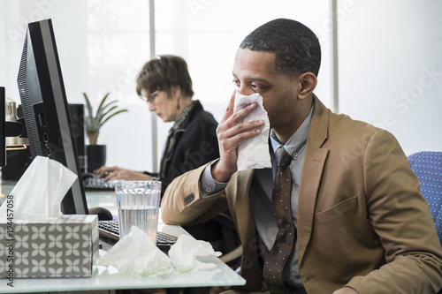 Fotografia  Business man coughing and sneezing in a small office