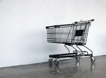Black Shopping Cart On The Floor And White Background. Trolley Is A Cart Supplied By A Shop, Especially Supermarkets, For Use By Customers For Transport  To Checkout Counter During Shopping.