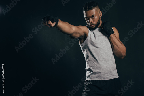 Valokuva  serious young african american kickboxer exercising isolated on black