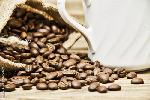 Fotografering  Spilled Coffee Beans on Wood