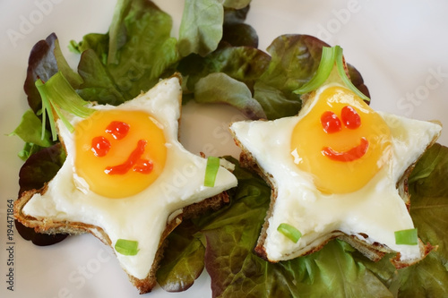 Fried eggs shaped as stars with funny faces on salad leaves. Breakfast for kids