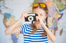 Pretty Little Girl In Striped T-shirt Takes Picture On Vintage Camera On The Background Of World Map