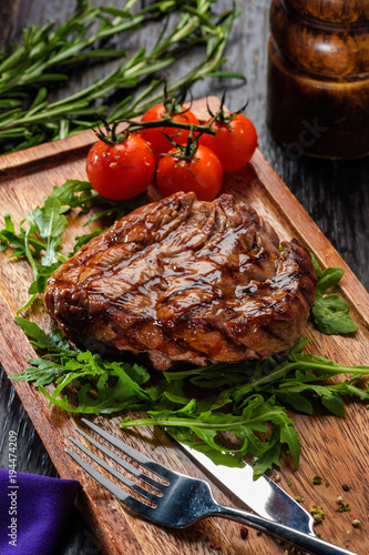 Deurstickers Steakhouse Grilled beef steak on wooden cutting board.