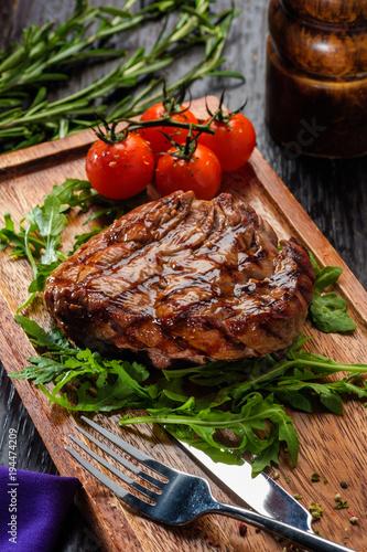 Grilled beef steak on wooden cutting board.