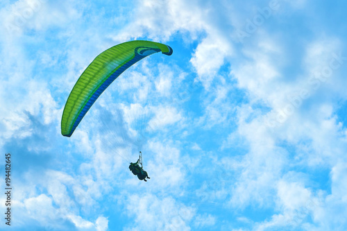 Foto op Aluminium Luchtsport Landscape of mountains against the blue sky and white clouds. Sun rays. One paratrooper flying over the mountain massif against the blue sky