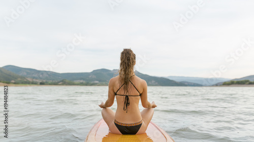 Young and sportive woman getting a relax moment on SUP board at sunset.