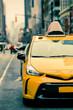New York City street scene with yellow taxi cab on urban street