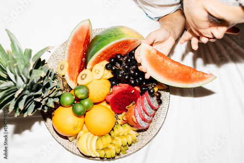 large fruit tray on bed with woman eating watermelon shot from above