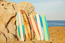 Vintage Surfboards Leaning Up Against Rocks On Beach In Mexico