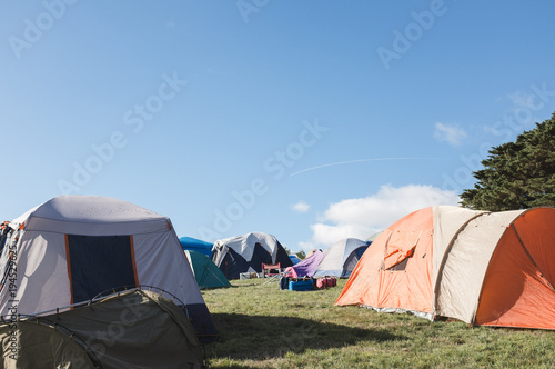multiple tents set up camping on grass with a blue sky
