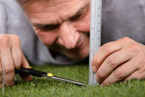 Fotografía  Man Using Measuring Scale While Cutting Grass