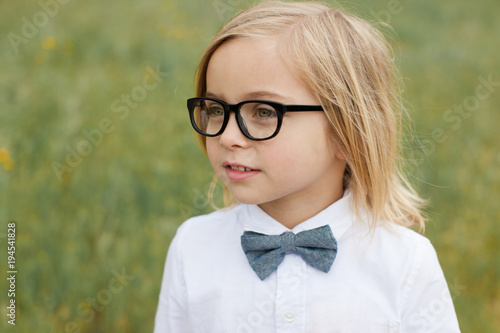 Cute fashionable boy in glasses and bowtie