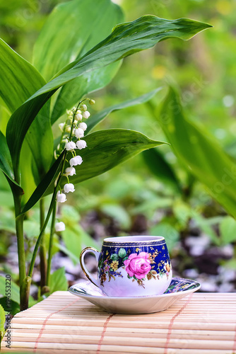 Poster Muguet de mai Beautiful fairy picture with a cup of tea and lilies of the valley