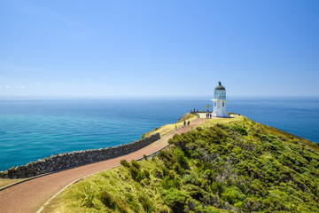 Stunning wide angle view of Cape Reinga Lighthouse and the path leading to it at Cape Reinga, the northernmost point of the North Island of New Zealand. The lighthouse is a famous tourist attraction.