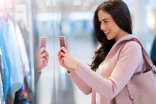 Fotografia  Woman using mobile phone in shopping mall