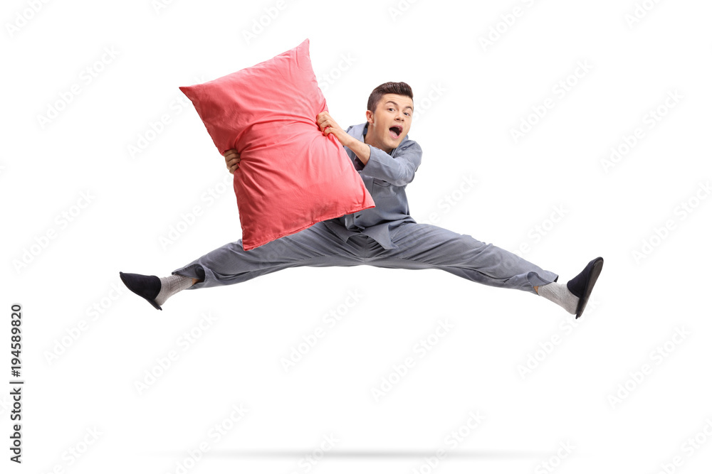 Fototapety, obrazy: Overjoyed teenager in pajamas holding a pillow and jumping