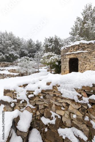 Fotografía  mur en pierres sèches et capitelle sous la neige