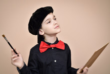 Thoughtful Young Painter With Red Bow Tie And Black Shirt And Cap Holding Paint Brush And Art Palette