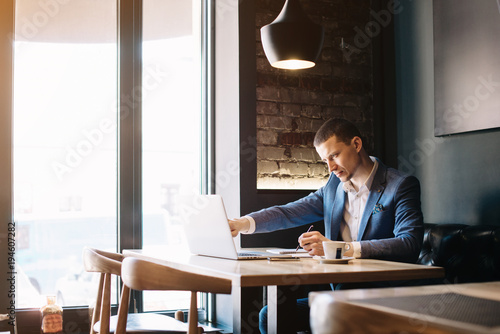 Foto  Serious businessman thinking over his plans connected with new projects and startups, checking e-mail, social networks, timetable, plans for week