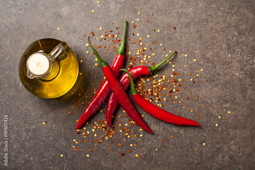 Staande foto Hot chili peppers Red chili pepper and pitcher of oil on stone background