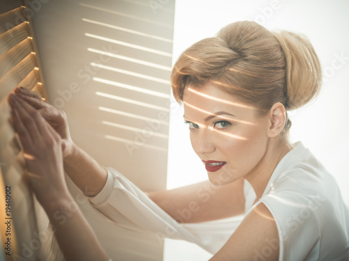 Fotografía  Woman with interested face with makeup going spy through jalousie
