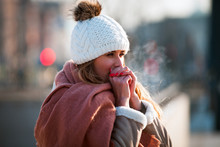 Woman Breathing On Her Hands To Keep Them Warm At Cold Winter