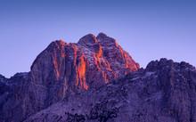 Sunset Light On Jof Fuart Peak From Valbruna Town. Julien Alps, Italy