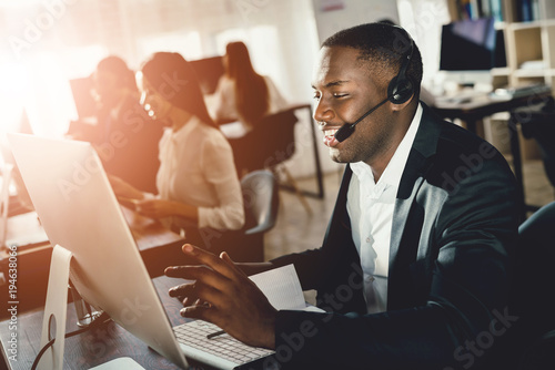 Fototapeta A black guy works in a call center. obraz