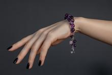 женская кисть руки с черным лаком на ногтях и красивым браслетом из сиреневых драгоценных камней