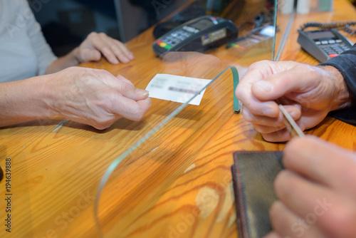 Ticket being passed under glass partition