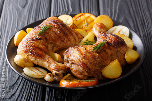 Hot fried chicken legs with grilled oranges, lemon, onion, garlic and potatoes close-up. horizontal