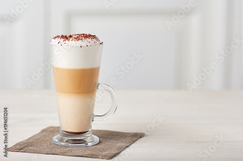 Fotografering Glass cup of coffee latte on wooden table