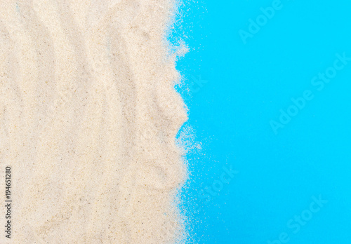 Sand on blue background. Copy space for text. Top view.