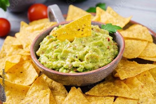 Guacamole avocado, lime, tomato, onion and cilantro, served with nachos - Traditional Mexican snack.