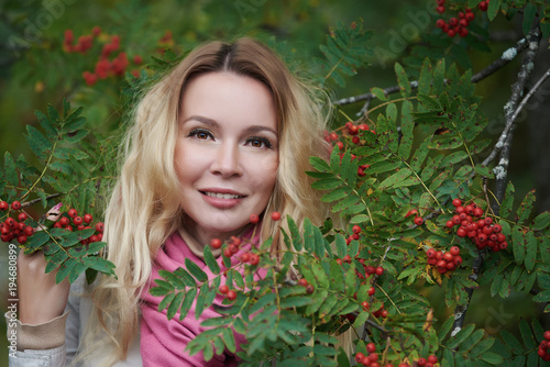 Portrait of a beautiful young woman in a ash berry bush. Canvas Print