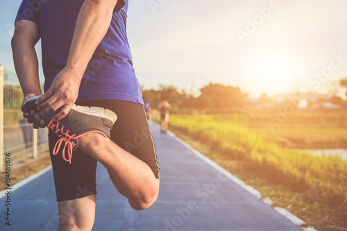 Foto  Man workout and wellness concept : Asian runner warm up his body before start running on road in the park