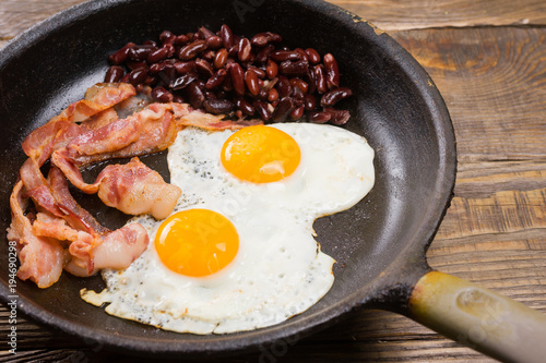 Foto op Plexiglas Gebakken Eieren Bacon,Egg and bean. Salted egg and sprinkled with black pepper. English breakfast. Grilled bacon, two eggs and beans in pan on wooden table