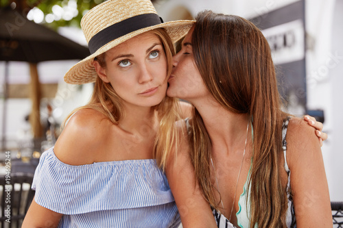 Fotografie, Obraz  Portrait of fashionable young females lesbians have passionate kiss, have good relationships, demonstrate true love, recreat together against outdoor cafe interior