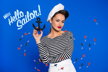 Portrait Of Fashionable Young Woman In Retro Clothing With Anchor In Hand And Well Hello Sailor Inscription Isolated On Blue