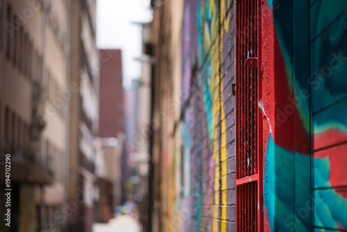 An abstract view of an inner city allyway  in Johannesburg, brightly decorated with colourful graffiti, focussed on the foreground and blurred in the distance