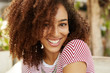Headshot of adorable beautiful female with curly hair and pleasant smile, wears striped t shirt, has white even teeth, being in good mood after date with boyfriend. People, ethnicity and positiveness
