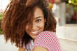 Sideways portrait of happy smiling female with curly bushy hairstyle dressed casually, thinks about something pleasant, enjoys summer rest in resort country. Happiness and positive emotions.